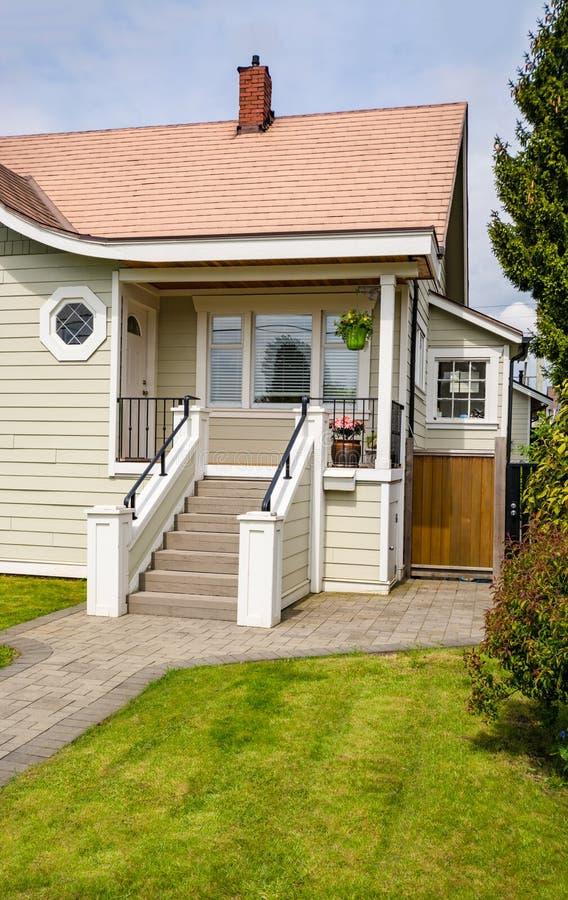 Hoofdingang van klein woonhuis met bedekte gang over groen gazon van voorwerf stock fotografie
