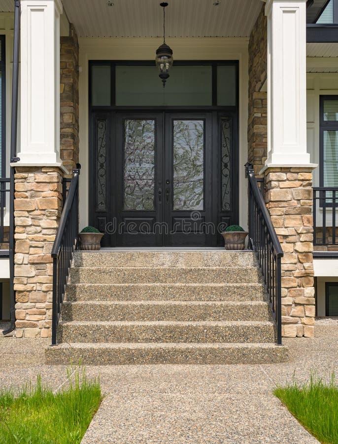Hoofdingang van woonhuis met deurstappen en bloempotten bij de deur royalty-vrije stock fotografie
