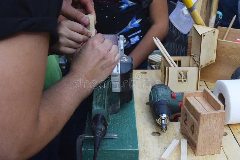 Hoofdklasse in timmerwerk opleiding Hulpmiddelen en de handen van de timmerman Het bejaarde timmerman werken stock foto's