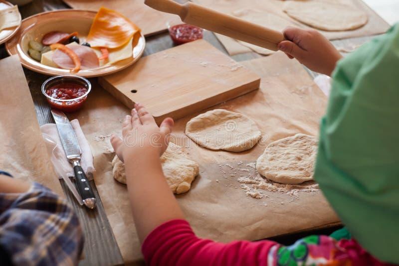 Hoofdklasse voor kinderen bij het bakken van grappige Halloween-pizza De jonge kinderen leren om een grappige monsterpizza te kok royalty-vrije stock afbeelding
