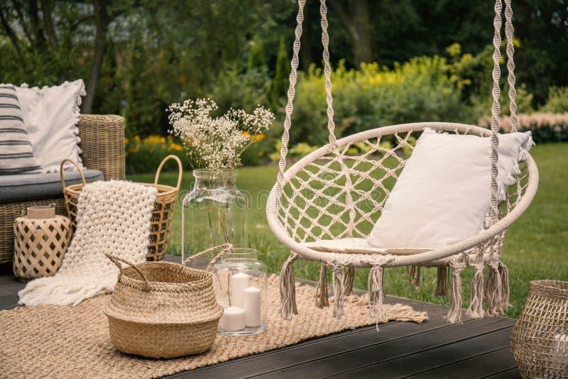 Hoofdkussen bij het hangen van stoel en mand op tapijt in tuindurin stock foto's