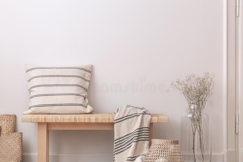 Hoofdkussen en deken op houten bank naast bloemen in beige minimaal vlak binnenland Echte foto royalty-vrije stock afbeeldingen