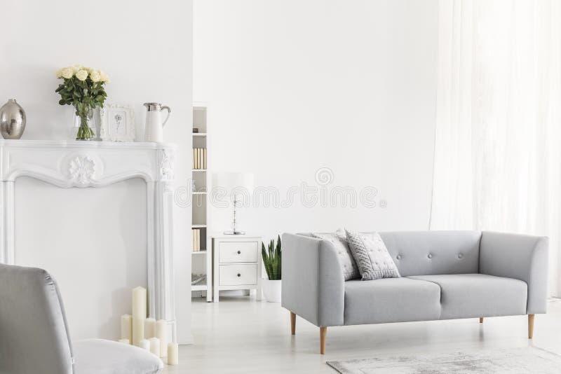 Hoofdkussens op grijze sofa en stoel in helder wit woonkamerbinnenland met bloemen en kaarsen Echte foto stock afbeeldingen