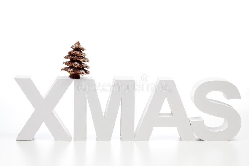Hoofdletters die woordkerstmis op de hoogste boom van chocoladekerstmis vormen tegen witte achtergrond stock afbeelding