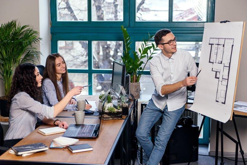 Hoofdmachinist die over nieuw creatief idee in de bouwtekeningen spreken terwijl vrouwelijke medewerker twee die van in het notit stock fotografie