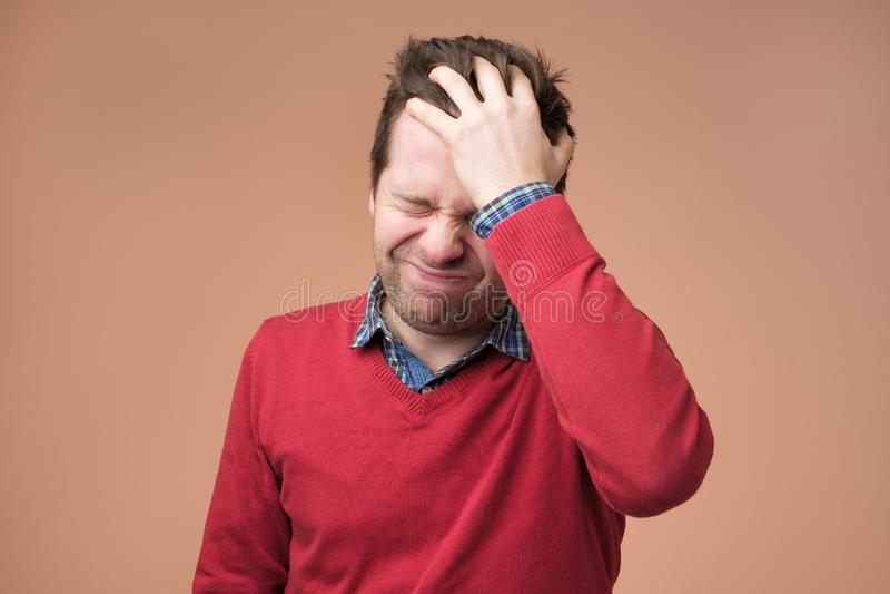 Hoofdpijn en migraine, mens met hoofdpijn op bruine achtergrond royalty-vrije stock foto's