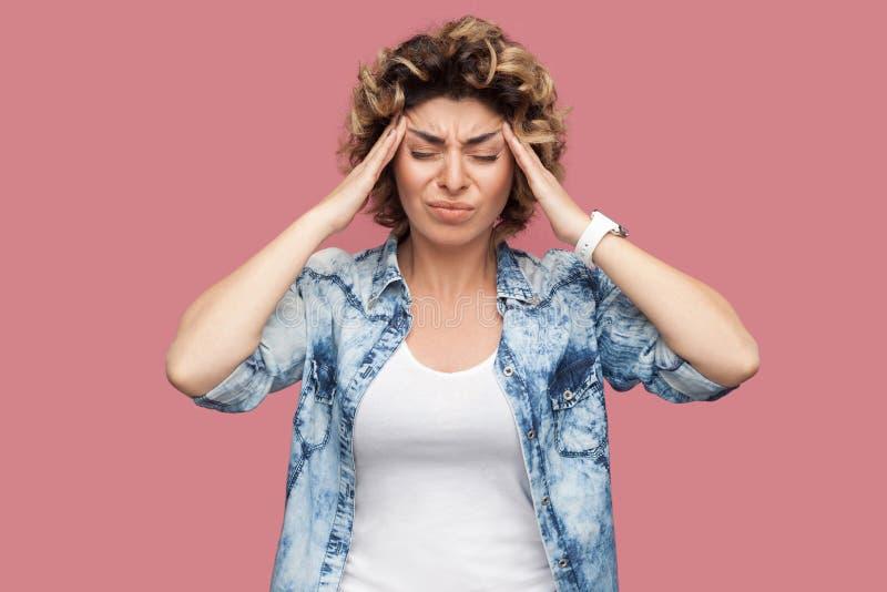 Hoofdpijn, het denken of verwarring Portret van droevige jonge vrouw met krullend haar in toevallig blauw overhemd die en haar pi stock foto's