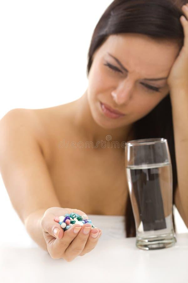 Hoofdpijnmeisje met in hand pillen stock afbeelding