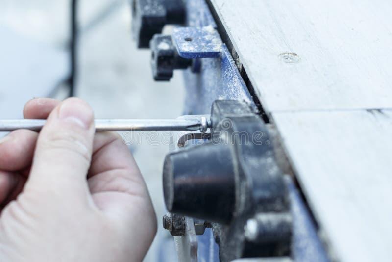 hoofdschroevedraaier om de machine te demonteren Zaag voor scherp hout royalty-vrije stock afbeelding