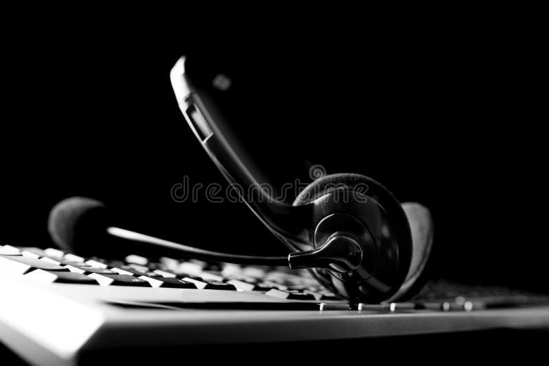 Hoofdtelefoon die op een computertoetsenbord liggen stock afbeelding