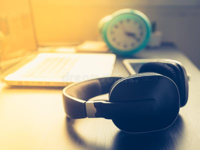 Hoofdtelefoon met Laptop op bureau en zonneschijn in middag stock afbeelding