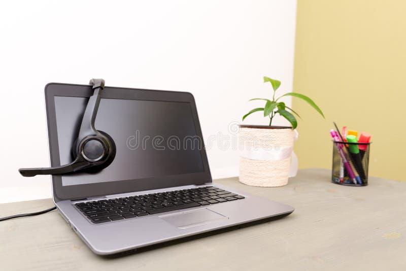 Hoofdtelefoon op laptop computer, concept voor mededeling, het suppor stock foto's