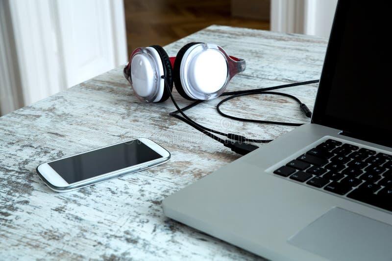 Hoofdtelefoons en een Laptop computer op een Desktop stock fotografie