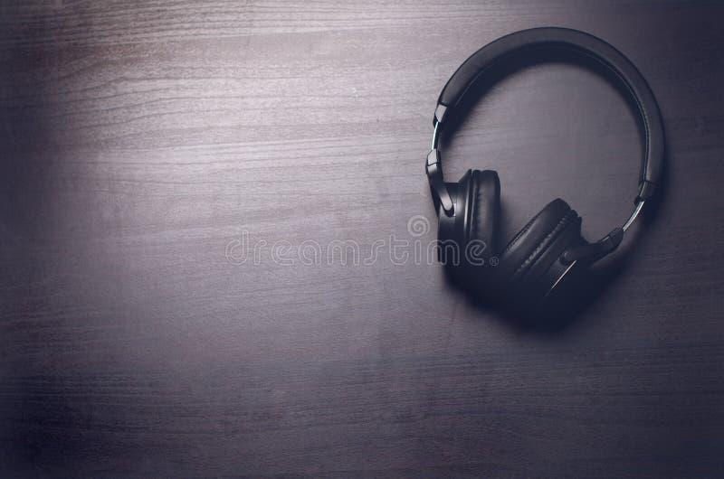 Hoofdtelefoons op een donkere achtergrond Muziektoebehoren Bluetooth-hoofdtelefoons zonder kabel stock fotografie