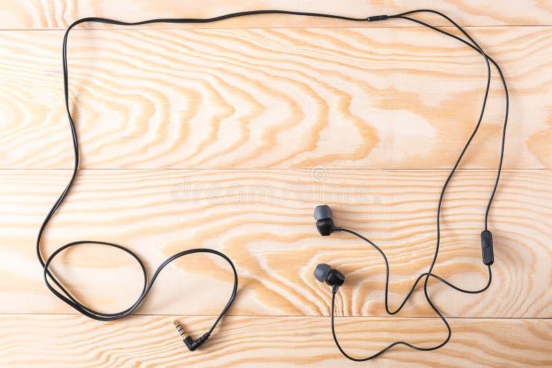 Hoofdtelefoons op een houten achtergrond stock afbeelding