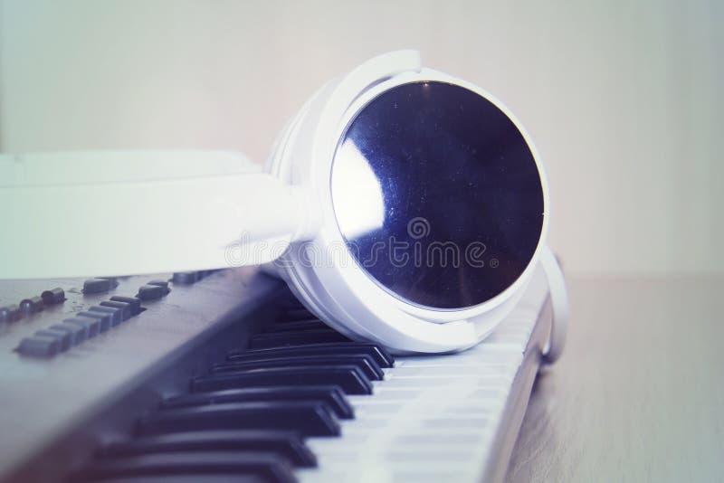 Hoofdtelefoons op muzikaal synthesizertoetsenbord Hoofdtelefoons op elektronische piano royalty-vrije stock fotografie