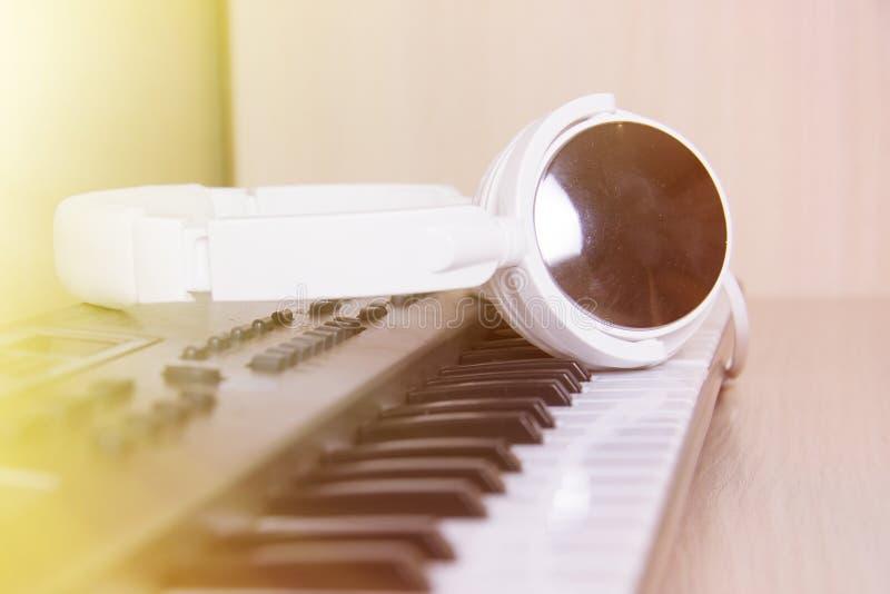 Hoofdtelefoons op muzikaal synthesizertoetsenbord Hoofdtelefoons op elektronische piano royalty-vrije stock afbeelding