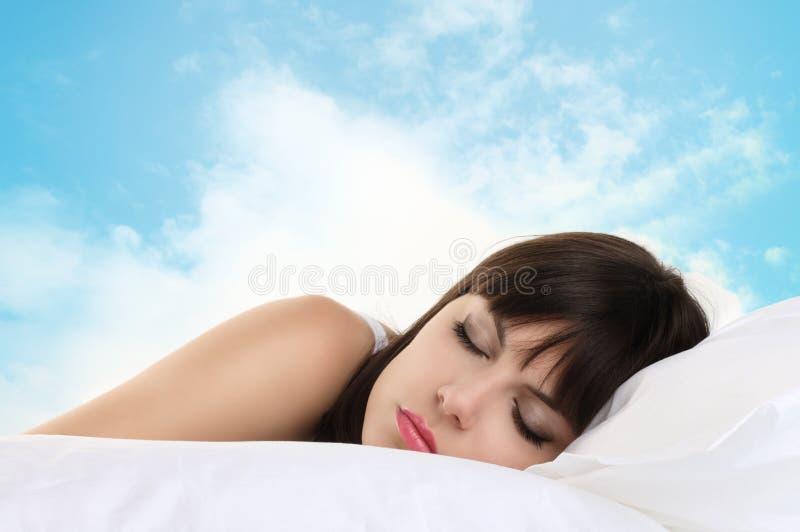 Hoofdvrouwenslaap op hoofdkussen met blauwe hemel op achtergrond stock foto's