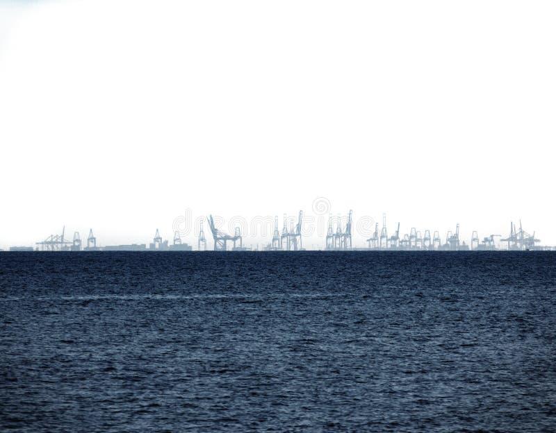 Hoog contrast van havenkranen in de overzeese horizon stock afbeeldingen