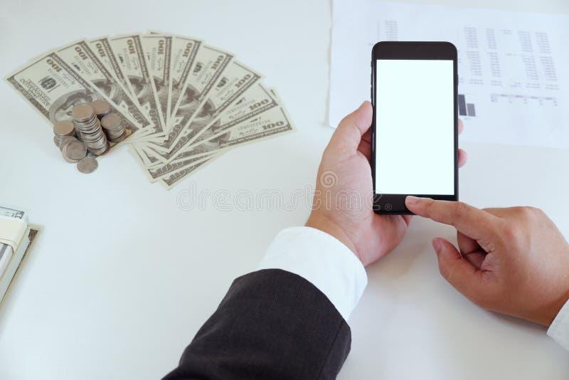 Hoog-hoek van de mens die smartphone in bureau met geld op werkend bureau gebruiken stock fotografie