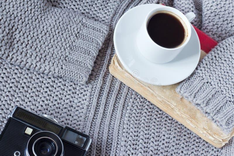 Hoog-hoek van een witte ceramische kop met witte koffie, boek en een oude camera van een trui wordt geschoten die stock afbeelding