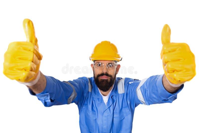 Hoog hoekportret van knappe hipster gebaarde bouwer die in bouwvakker en transparante veiligheidsbril twee duimen omhoog binnen o stock fotografie