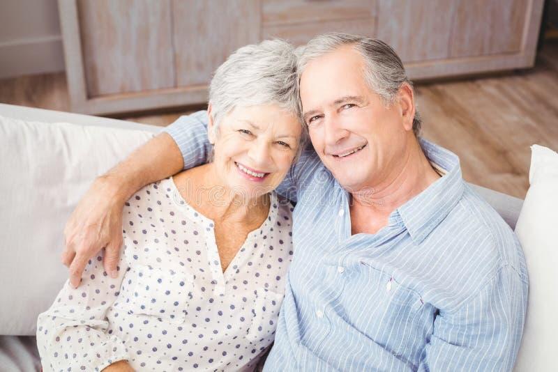 Hoog hoekportret van romantische hogere paarzitting op bank stock foto's