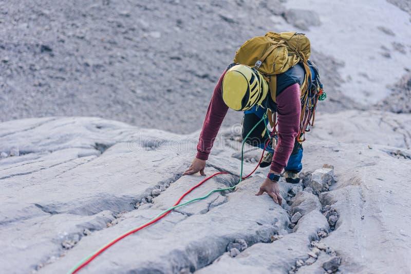 Hoog hoekschot van een persoon die een rots in de Alpen in Oostenrijk beklimt - het oplossen van uitdagingen concept stock fotografie