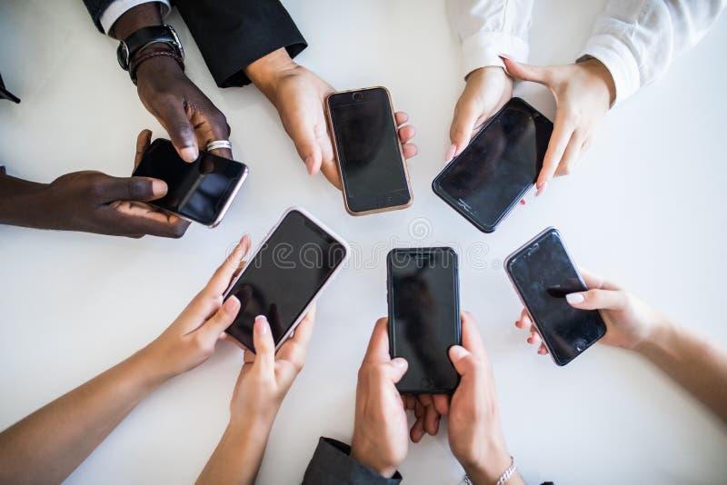 Hoog Hoekweergeven van Zakenluihand die Mobiele Telefoons met behulp van Verslaving op netwerken stock foto's