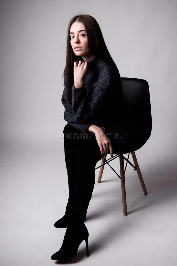 Hoog manierportret van jonge elegante vrouw sittung op stoel zwarte die kleren op witte achtergrond wordt geïsoleerd stock afbeeldingen