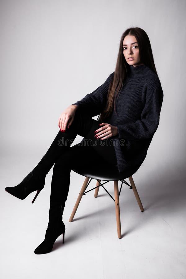 Hoog manierportret van jonge elegante vrouw sittung op stoel zwarte die kleren op witte achtergrond wordt geïsoleerd stock afbeelding