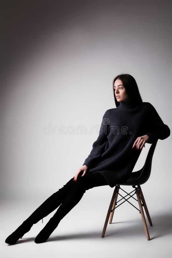 Hoog manierportret van jonge elegante vrouw sittung op stoel zwarte die kleren op witte achtergrond wordt geïsoleerd royalty-vrije stock afbeelding