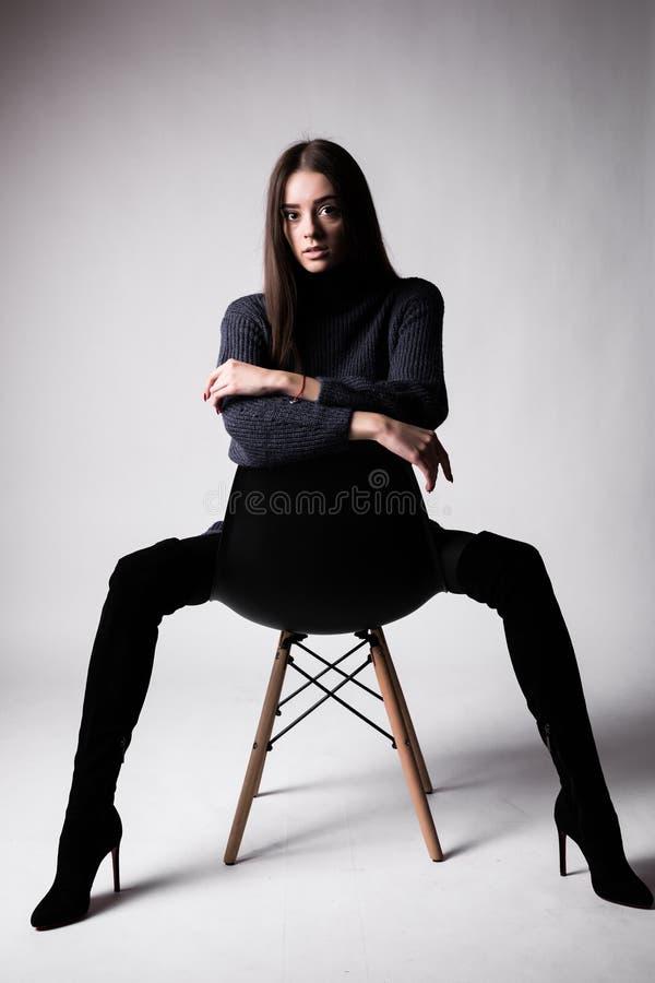 Hoog manierportret van jonge elegante vrouw sittung op stoel zwarte die kleren op witte achtergrond wordt geïsoleerd stock foto's