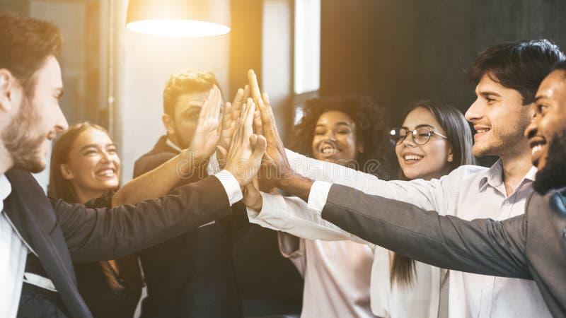 Hoog-vijf voor succes Diverse groep bedrijfscollega's in bureau stock foto's