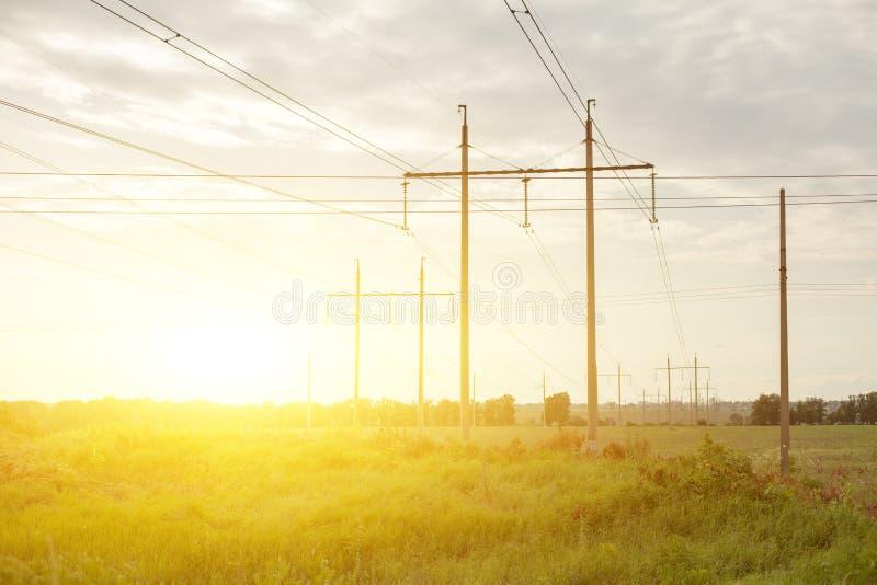 Hoogspanningslijnen en machtspylonen in een vlak en groen landbouwlandschap op een zonnige dag royalty-vrije stock fotografie