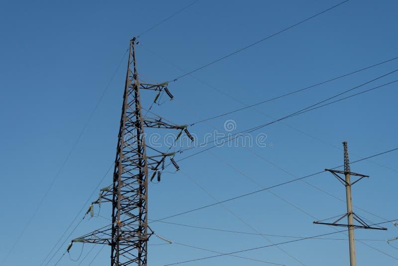 Hoogspanningslijnen en machtspylonen op de industriezone op een Zonnige dag met een duidelijke blauwe hemel stock foto's