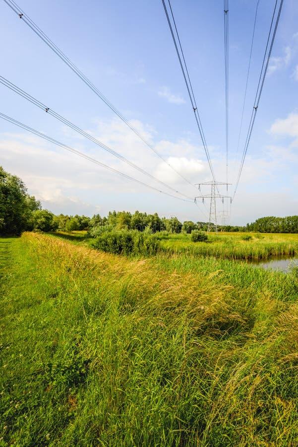 Hoogspanningslijnen en pylonen in een landelijk Nederlands landschap royalty-vrije stock afbeelding