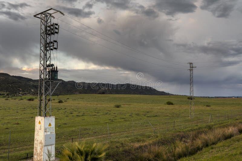 Hoogspanningspolen in een groen aardlandschap royalty-vrije stock afbeeldingen