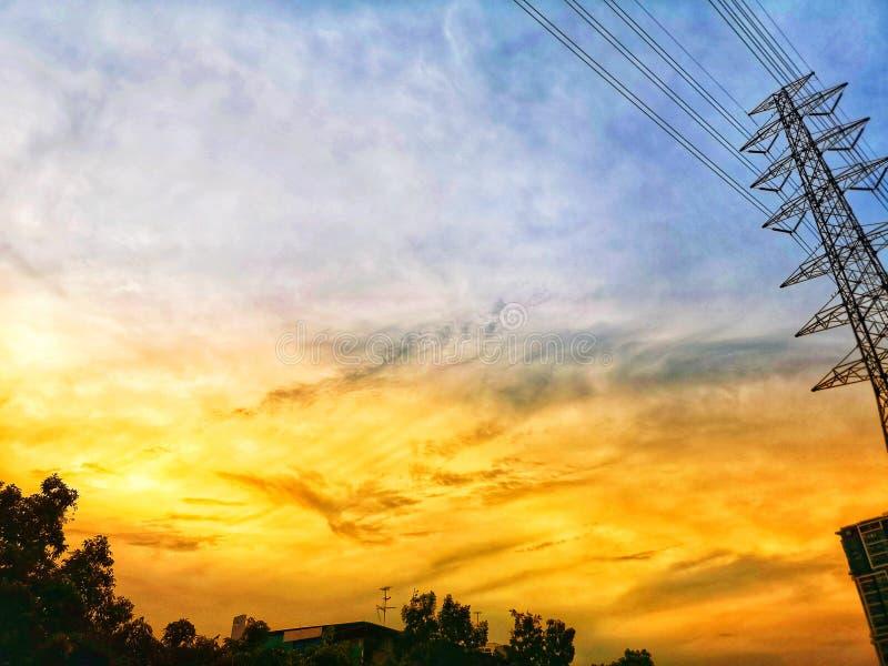 hoogspanningspool op de aard ‹van de orangeand†zonsondergang ‹blue†‹sky†‹background†royalty-vrije stock afbeeldingen
