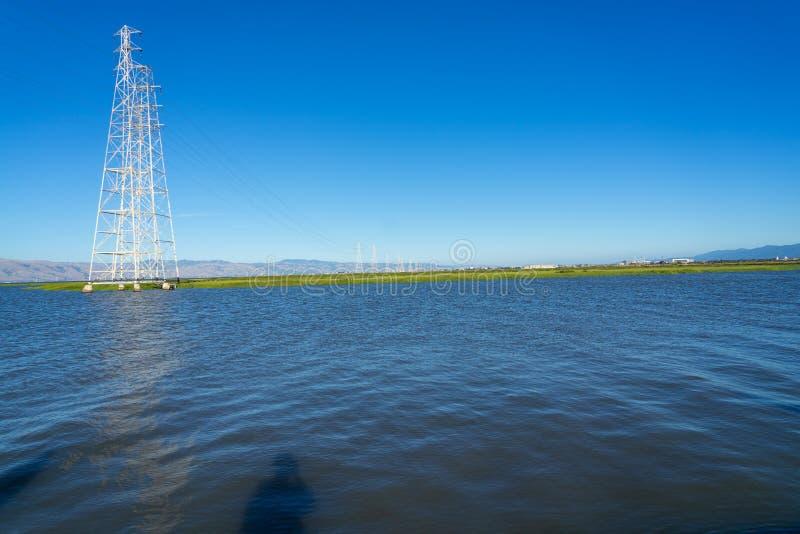 Hoogspanningspost, Hoogspanningstoren bij blauwe aardige hemel en overzees - Palo Alto, Californië, de V.S. stock afbeeldingen