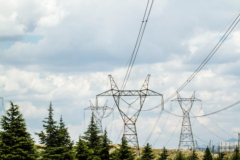 Hoogspanningspowerlines en pylonen tegen bewolkte hemel royalty-vrije stock foto
