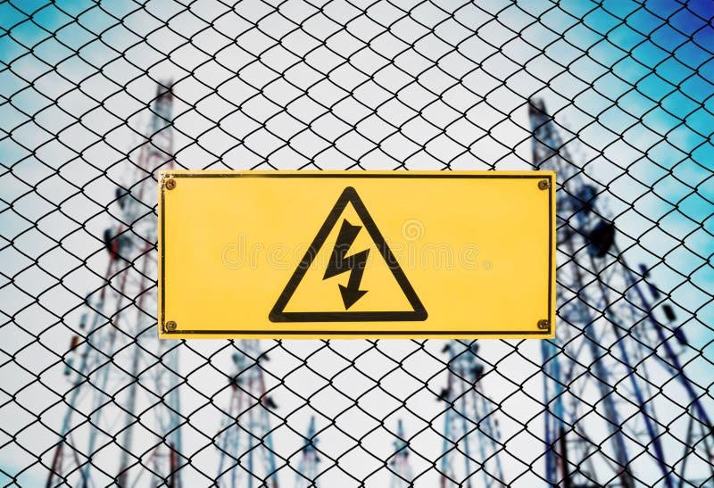 Hoogspanningsteken en het Uithangbord van de Symboolvoorzichtigheid op Omheining Wire bij Elektroelektrische centralepost royalty-vrije stock afbeeldingen