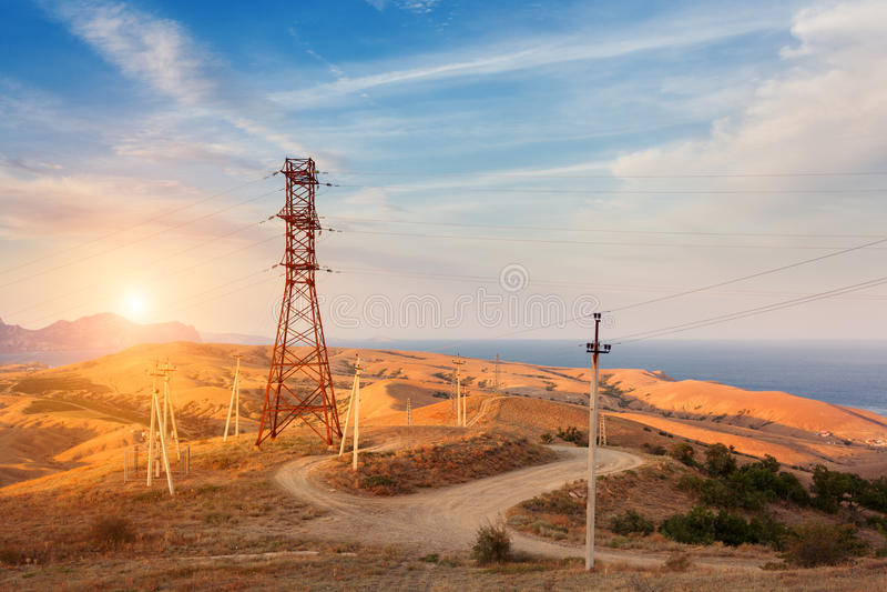 Hoogspanningstoren in bergen bij zonsondergang Elektriciteits pylon systeem royalty-vrije stock foto