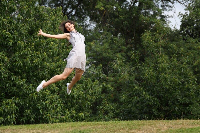 Hoogspringen in bomen voor succes van mooi meisje royalty-vrije stock foto's
