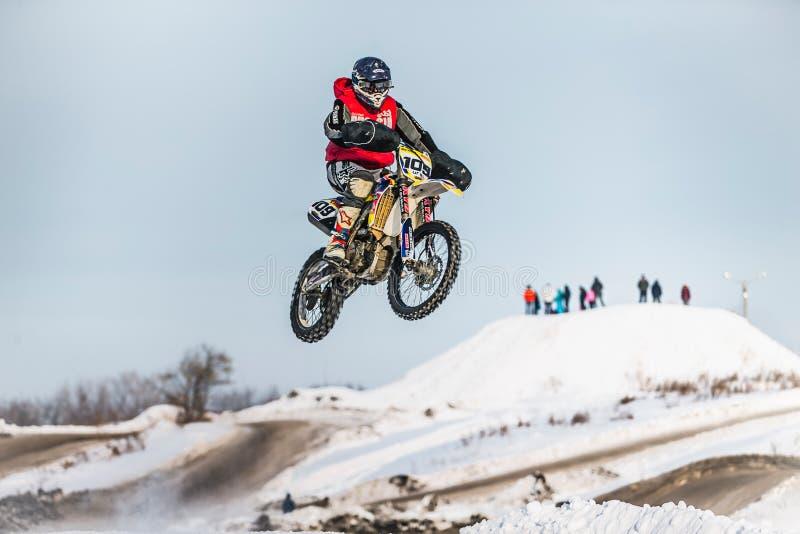 Hoogspringenmotorracer op sneeuw behandelde heuvel stock afbeeldingen