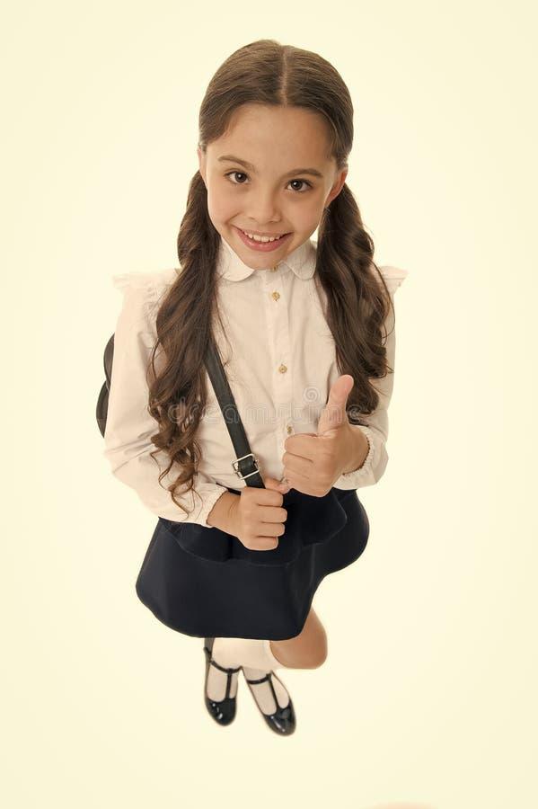 Hoogst adviseer Het schoolmeisje toont duim op gebaar, geïsoleerde witte achtergrond Meisje gelukkige het glimlachen aanbeveling  royalty-vrije stock afbeelding