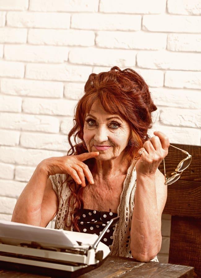Hoogst ervaren Hogere schrijver bij bureau Oude verslaggever of journalist die op schrijfmachine schrijven Het oude vrouwenwerk i royalty-vrije stock foto