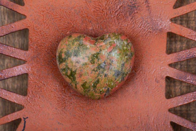 Hoogst opgepoetst gezwollen Unakite-Hart van Unakas-Bergen in Noord-Carolina, op Rustieke Oranje plaat stock foto's