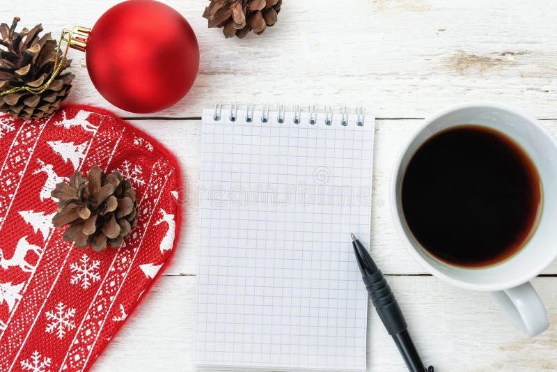 Hoogste beeld van open notitieboekje met blanco pagina's, naast denneappels, rode Kerstmisbal en kop van koffie over houten lijst stock foto's