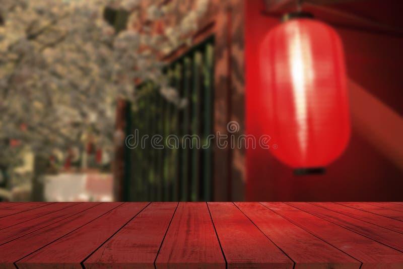 Hoogste bureau met de rode achtergrond van het lamponduidelijke beeld, houten lijst stock fotografie